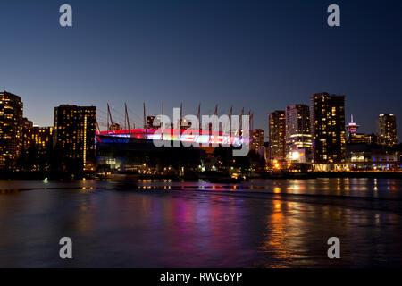 BC Place Stadium und Vancouver City Skyline auf False Creek. BC Place leuchtet mit internationalen Flaggen für die Kanada Sevens Rugby Turnier 2019. - Stockfoto
