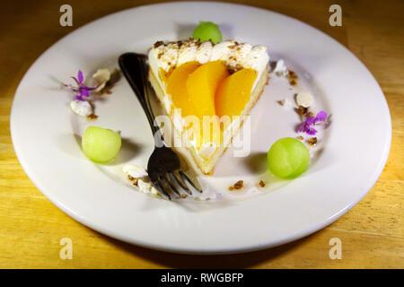 Pfirsich Torte und Creme. Eine Gabel liegt auf der Platte. - Stockfoto