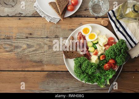 Platte für gesunde Ernährung, Frühstück oder Mittagessen Ansicht von oben. Kohl Kohl, Eier, Avocado, Speck, Tomaten, Rosenkohl, Blumenkohl Brot Toast auf Holz - Stockfoto