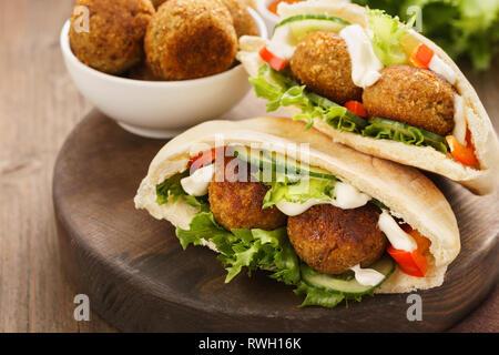Falafel und frisches Gemüse in pita Brot auf Holzbrett. - Stockfoto