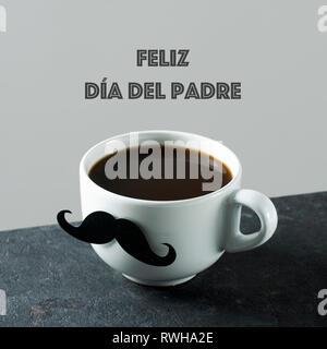 Der text Feliz dia del Padre, happy Vatertag in Spanisch, und eine weiße Keramik Tasse mit Kaffee, mit einem gefälschten Schnurrbart befestigt ist, auf einem dunklen Stein - Stockfoto