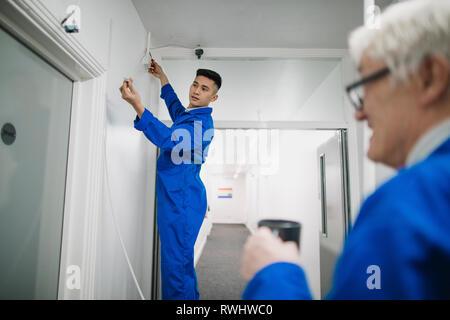 Auszubildender Elektriker ist gerade eine Überwachungskamera mit Hilfe von seinem Tutor. - Stockfoto