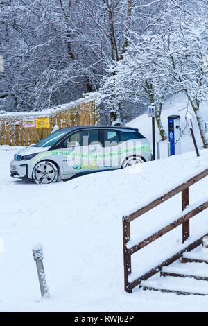 BMW-Elektroauto an elektrischen Auto aufgeladen Ladestation Punkt in verschneiten Parkplatz durch Clachaig Inn, Glencoe, Highlands, Schottland im Winter - Stockfoto