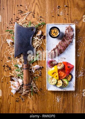 Barbecue Rib Eye Steak mit einem choper. Trocken im Alter von Entrecote Steak mit gegrilltem Gemüse. Ansicht von oben, kopieren. - Stockfoto