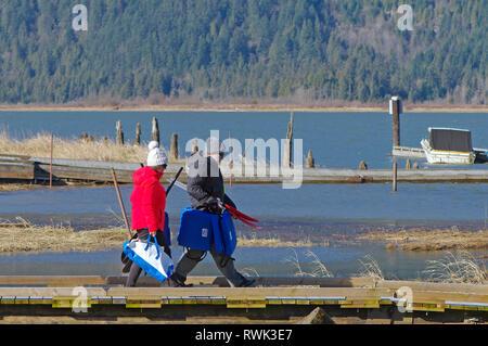 Paar mittleren Alters im Winter Kleidung wandern mit Schwimmwesten und Kajak Paddel entlang einem Pier in Grant verengt Regional Park, B.C., Kanada. - Stockfoto