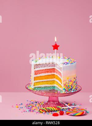 Bunte 2-in-1-Geburtstag Kuchen mit Streuseln und Süßigkeiten über einen rosa Hintergrund. - Stockfoto