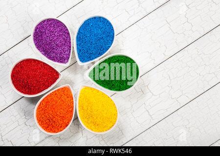 Ein Regenbogen Sortiment von bunten Streuseln Backen zum Dekorieren Kekse und Kuchen in Blütenblatt benutzt geformte Schüsseln - Stockfoto