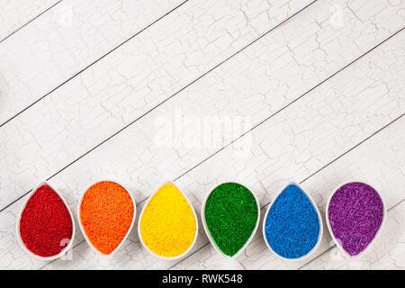 Ein Regenbogen Grenze von bunten Streuseln Backen in Blütenblatt geformte Schüsseln über einen weissen Hintergrund. - Stockfoto
