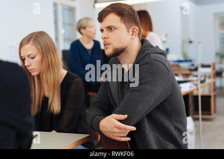 Junger Mann in einem business Meeting aufmerksam zuhören mit verschränkten Armen in einem großen, geräumigen Büro - Stockfoto