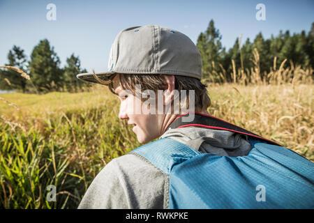 Teenager mit Rucksack im Bereich der langen Gras, Sandpoint, Idaho, USA - Stockfoto