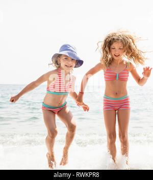 Zwei Schwestern in passenden bikini Plantschen im Meer, Capoliveri, Toskana, Italien - Stockfoto