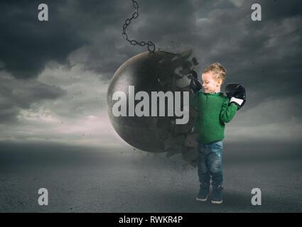 Kraft und Entschlossenheit eines Kindes gegen eine Abrissbirne - Stockfoto