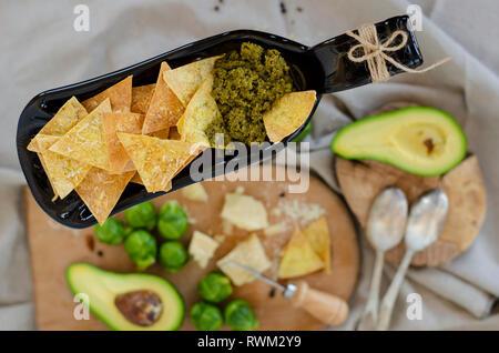 Avocado, Rosenkohl, Parmesan und Chips mit Pesto auf ungewöhnliche Servierteller. Ansicht von oben - Stockfoto