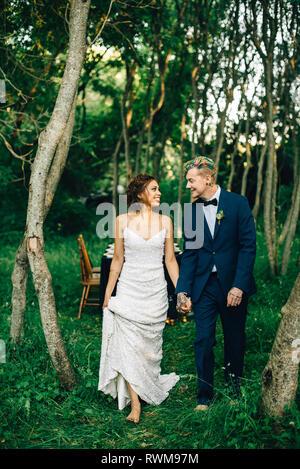 Romantische Braut und Bräutigam im Wald spazieren - Stockfoto