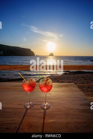 Aperol Spritz (Aperitif, Cocktail, bestehend aus Prosecco, Aperol und Sodawasser). Zwei Gläser auf den Tisch am Strand bei Sonnenuntergang - Stockfoto