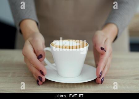 Barista in Schürze im Coffee Shop nur gebraut frischen Kaffee an Kunden geben. - Stockfoto