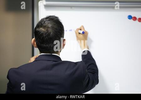 Ein Geschäftsmann auf einer Sitzung schriftlich auf eine Tafel mit einem Marker - Stockfoto