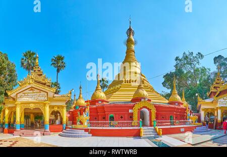 BAGO, MYANMAR - Februar 15, 2018: Panorama der Shwe Gu legen Pagode Grundstück mit Stupa und Bild Häuser in rot-gelben Farben mit vergoldeten Details und kom - Stockfoto