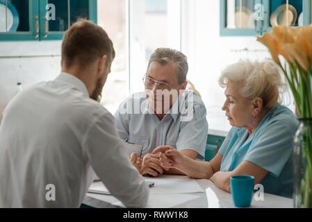 Ältere Eltern Beratung ihr Sohn, Finanzberater, bei sich zu Hause. Verkauf oder Kauf von Immobilien. - Stockfoto