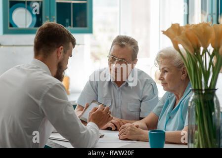 Alte Ehepaar im Gespräch mit einem Finanzberater in ihrer Heimat. Planen eines sicheren und angenehmen Ruhestand. - Stockfoto