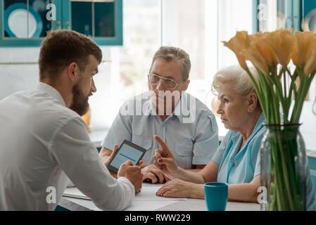 Senior Paar diskutiert mit Finanzberater zu Hause, um Fragen über Zukunft. - Stockfoto