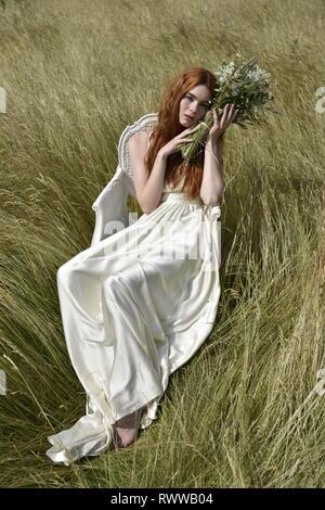 Eine schöne rothaarige Mädchen in einem langen weißen Kleid stellt in der Mitte eines Daisy-schönes Mädchen in ein Feld - Stockfoto