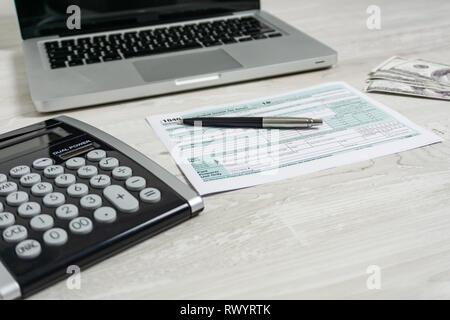 US-Steuer Formular neben Computer Laptop, Dollar, Rechnungen, Rechner und Steuerformular 1040. Steuern in Form us-Geschäft Einkommen office Hand auszufüllen Konzept - Stockfoto