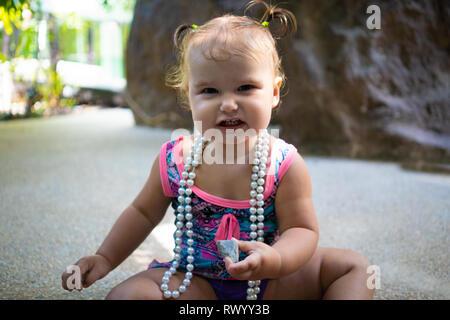 Ein Mädchen im Badeanzug mit weißen Perlen überrascht ist, freut sich, schreien, erhebt ihre Hände. Fashion Concept für Kinder. - Stockfoto