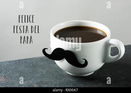 Der Text von Felice festa del Papa, happy Vatertag in Italienisch, und eine weiße Keramik Tasse mit Kaffee, mit einem gefälschten Schnurrbart befestigt ist, auf eine dunkle Ston - Stockfoto