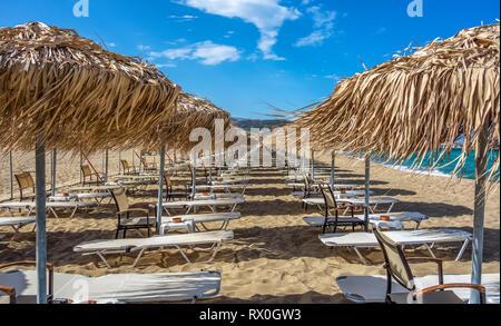 Reihen von Sonnenschirmen und Liegen am leeren Strand. Griechenland. Kreta - Stockfoto