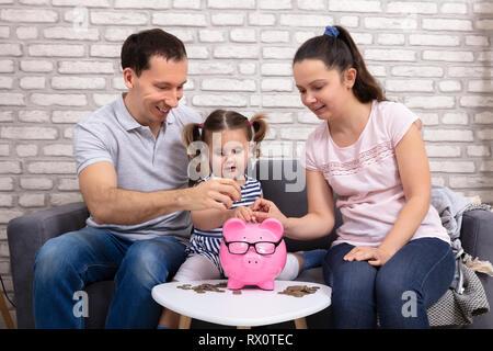 Glückliche Eltern mit Tochter einfügen Münze in rosa Sparschwein - Stockfoto