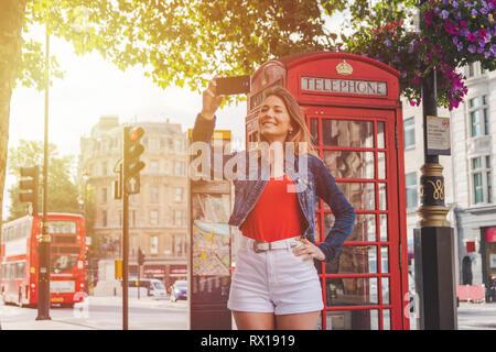 Gehweg in der Straße von England. Frau mit legere Kleidung. Phone Booth und Double Decker Bus als Hintergrund - Stockfoto