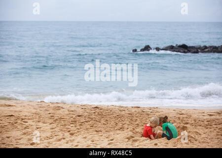Bruder und Schwester spielen mit Sand und Wasser an einem tropischen Strand, in schützenden Neoprenanzug bekleidet. Reisen mit Kindern, Beach hopping, Familie tim - Stockfoto