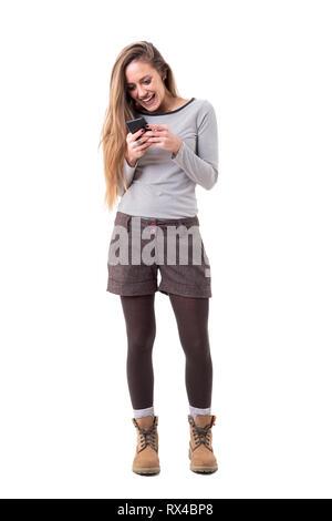 Freundliche neugierige junge stilvolle Frau Schreiben oder Lesen von Nachrichten auf dem Handy. Voller Körper auf weißem Hintergrund. - Stockfoto