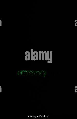 Grün metall Feder auf schwarzen Hintergrund mit Spiegelbild isoliert. Makro Foto - Stockfoto