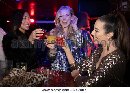 Junge Frauen Freunde toasten Cocktails in Nachtclub - Stockfoto