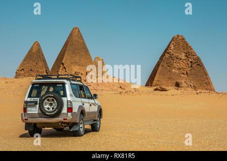 Nuri, Sudan, Februar 9., 2019: Off-road-Fahrzeug in der Wüste Sand vor drei Pyramiden im Sudan - Stockfoto