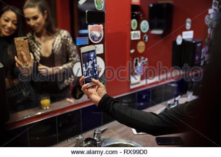 Frauen, die Freunde, die in der Diskothek selfie Badezimmer spiegel - Stockfoto