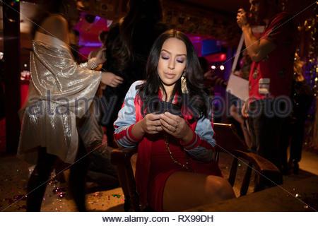 Frau mit smart phone in Nachtclub - Stockfoto