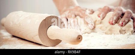 Frau tragen weiße Schürze Kneten mit Rolling Pin close-up weibliche Hände das Kochen backen Kuchen Torten Teig. Koch bei der Arbeit oder Hausfrau in der Ki - Stockfoto