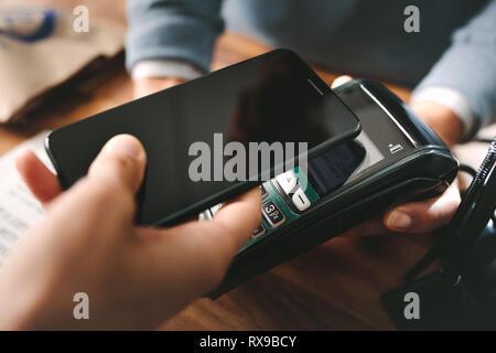 Kunde zahlt Rechnung durch das Smartphone mit der NFC-Technologie in der Apotheke. Nahaufnahme der weiblichen Hand ihr Handy über ein Kartenlesegerät Maschine f - Stockfoto