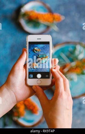 7/8 Hände von Frau fotografieren Sanddornbeeren mit Platten auf Tisch - Stockfoto