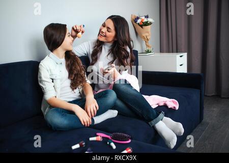 Schöne Brünette weißen Mutter und Tochter sitzen zusammen im Zimmer. Mama macht sich für Mädchen bilden. Sie Puder und Pinsel. Haarbürste und Nagellack - Stockfoto