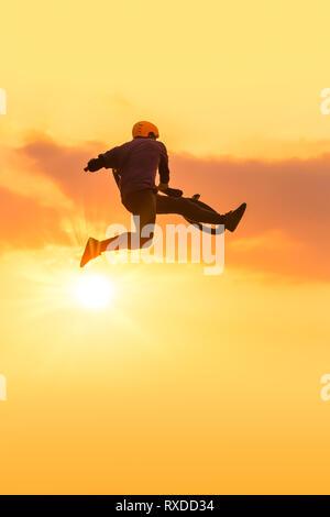 Beleuchtete Silhouette des Menschen tricks Ausführung in einer bmx springen. Sonnenuntergang Spaß - Stockfoto