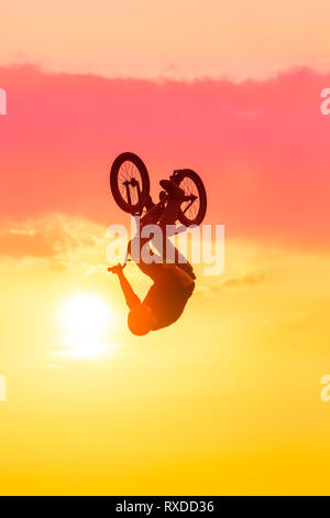 Silhouette der Mann die Tricks auf BMX Bike gegen rosa Sonnenuntergang Himmel - Stockfoto