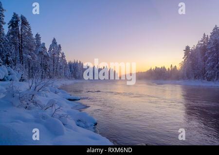 Dunst und Nebel steigen vom offenen Wasser eines strömenden Fluss während eines kalten und klaren Sonnenuntergang bei -30° C, Kiveskoski Fluss, Kuusamo, Finnland