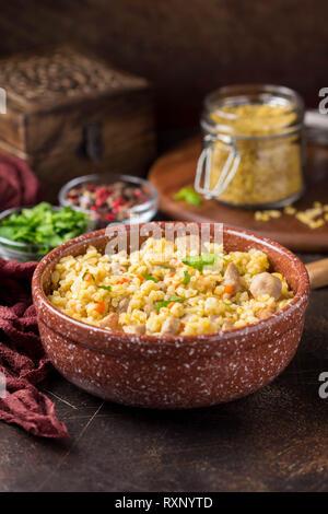 Bulgur mit der Türkei, Schwein oder Rind. Östlichen Reisgericht mit köstlichen Speisen. Geschmortes Fleisch mit Grütze. Pilav auf dunklem Hintergrund - Stockfoto