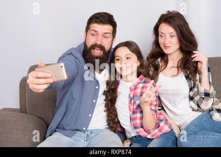 Verwendung des Smartphones für selfie. Freundliche Familie gemeinsam Spaß zu haben. Mama, Papa und Tochter entspannt auf einer Couch. Familie posieren für Fotos. Glückliche Momente festzuhalten. Familie selfie. Familie verbringen Wochenende zusammen. - Stockfoto