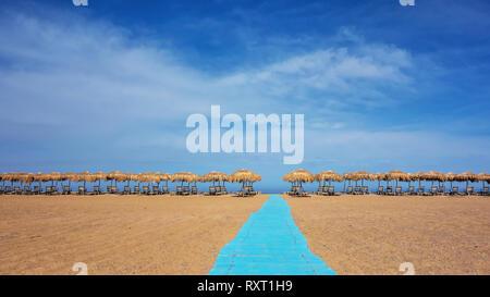Sonnenschirme und Liegestühle an sonnigen leeren Strand. Griechenland. Kreta - Stockfoto