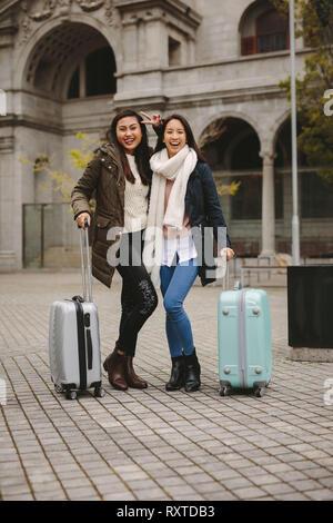 Zwei weibliche Touristen auf der Straße stehen, ihr Gepäck Taschen und Spaß zu haben. Fröhliche Frau touristische, die Gesichter in der Straße stehen mit ihren Frie - Stockfoto